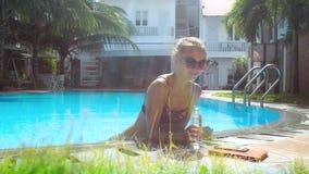 La muchacha toma la botella de agua y bebe inclinarse en barrera de la piscina almacen de video