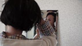 La muchacha toma cuidado de su pelo almacen de metraje de vídeo