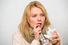 La muchacha toma el agua de la bebida de la medicina Dolor de cabeza y medicinas anticatarrales El control despeinado mujer de la foto de archivo
