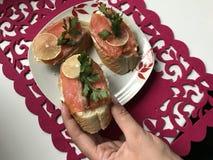 La muchacha toma el bocadillo de la placa Bocadillos con los salmones, adornados con verdes y el limón Bocadillos en una placa, s Foto de archivo