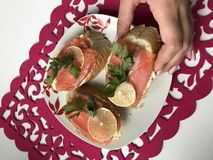 La muchacha toma el bocadillo de la placa Bocadillos con los salmones, adornados con verdes y el limón Bocadillos en una placa, s Imagen de archivo