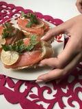 La muchacha toma el bocadillo de la placa Bocadillos con los salmones, adornados con verdes y el limón Bocadillos en una placa, s Fotografía de archivo