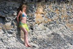 La muchacha toma el sol cerca de la roca Imágenes de archivo libres de regalías