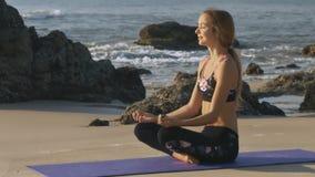La muchacha toma el sol en actitud de la yoga contra olas oceánicas metrajes