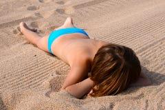 La muchacha toma el sol en la playa Imagen de archivo libre de regalías