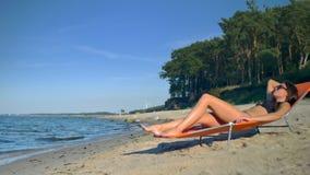 La muchacha toma el sol en la playa almacen de video