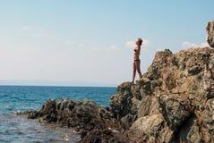 La muchacha toma el sol en una roca imagenes de archivo