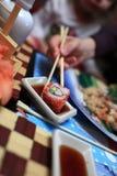 La muchacha toma el sushi imagen de archivo