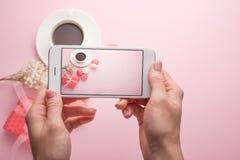 La muchacha toma imágenes en un teléfono en un fondo rosado del café y de los macarrones, para un instagram imágenes de archivo libres de regalías