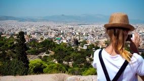 La muchacha toma a imágenes una vista de la ciudad de Atenas almacen de video