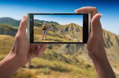 La muchacha toma a imagen del caminante en las montañas imágenes de archivo libres de regalías