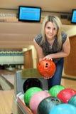 La muchacha toma la bola de dos manos para jugar al bowling Foto de archivo libre de regalías