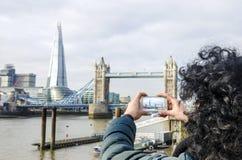 La muchacha toma la imagen del casco y del puente de la torre Fotos de archivo