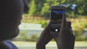 La muchacha toma las fotos de la naturaleza a través de ventana del autobús almacen de video