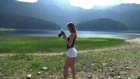 La muchacha toma soportes de una imagen contra la perspectiva del paisaje almacen de video