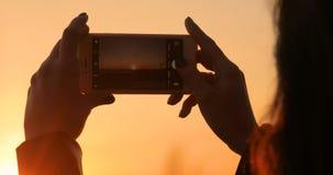La muchacha toma una imagen de una puesta del sol hermosa en un teléfono móvil almacen de video