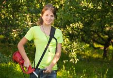 La muchacha trabaja con el hierba-cortador Fotos de archivo