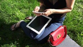 La muchacha trabaja con la tableta y el teléfono celular en el parque almacen de video