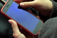 La muchacha trabaja con un smartphone rojo Primer Pantalla del teléfono móvil en manos femeninas Copie el espacio Fondo para una  fotografía de archivo libre de regalías