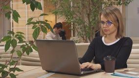 La muchacha trabaja en el ordenador portátil en el eje almacen de video
