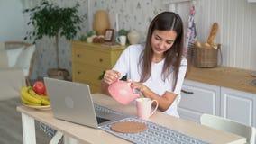 La muchacha trabaja en el ordenador portátil, vierte té de la taza en sus manos, cámara lenta de la caldera y de los controles metrajes