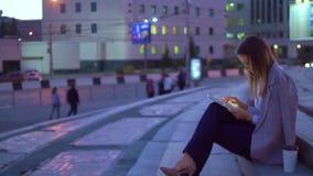 La muchacha trabaja en la tableta, por la tarde en el centro de ciudad almacen de metraje de vídeo