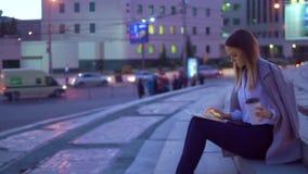 La muchacha trabaja en la tableta, por la tarde en el centro de ciudad, bebiendo el café metrajes