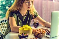 La muchacha trabaja en un ordenador y come los alimentos de preparaci?n r?pida foto de archivo
