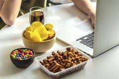 La muchacha trabaja en un ordenador y come los alimentos de preparaci?n r?pida fotos de archivo