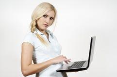 La muchacha trabaja en una computadora portátil Imagen de archivo libre de regalías
