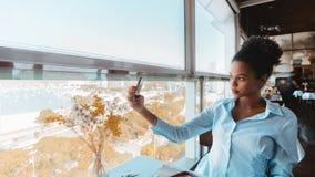 La muchacha trasera está tomando el selfie en café cerca de ventana Foto de archivo libre de regalías