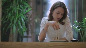 La muchacha trastornada come el jengibre en un restaurante japonés almacen de video
