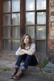 La muchacha triste con el pelo largo en vaqueros de trece se sienta cerca de ventana grande Imagen de archivo