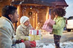 La muchacha triste con los padres mira decepcionado una Navidad presen Fotos de archivo