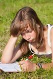 La muchacha triste está mintiendo en hierba verde Fotografía de archivo