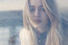 La muchacha triste hermosa con los ojos grandes en una capa está detrás de vidrio mojado fotos de archivo libres de regalías