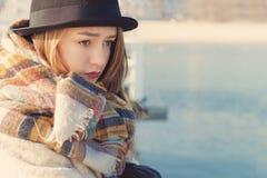 La muchacha triste joven hermosa del retrato retro en sombrero y capa se coloca en el muelle Fotos de archivo