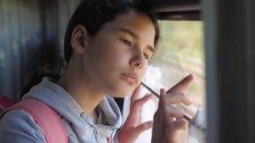 La muchacha triste mira hacia fuera la ventana del tren concepto del ferrocarril del transporte del viaje faltas adolescentes de  metrajes