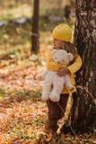 La muchacha triste que se coloca en el abedul en bosque del otoño y los abrazos llevan el juguete Imagenes de archivo