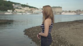La muchacha triste se coloca en el banco del río almacen de video