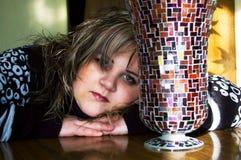 La muchacha triste se sienta cerca de un florero fotos de archivo libres de regalías