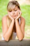 La muchacha triste se sienta en banco Fotos de archivo