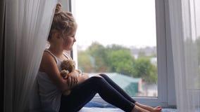 La muchacha triste se sienta en el alféizar almacen de metraje de vídeo