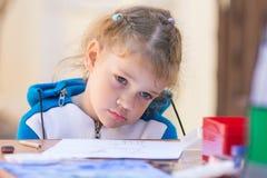 La muchacha triste se sienta en una tabla en el patio de la casa y no quiere dibujar Imagen de archivo libre de regalías