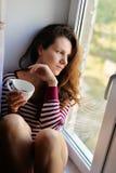 La muchacha triste se sienta en una ventana con una taza de té, café Fotos de archivo