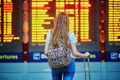 La muchacha turística con la mochila y continúa el equipaje en aeropuerto internacional, cerca de tablero de la información del v