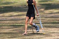 La muchacha turística del accidente está caminando por las muletas en el jardín Fotografía de archivo libre de regalías