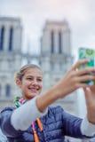 La muchacha turística del adolescente está tomando el selfie con la catedral de Notre Dame de Paris francia Foto de archivo