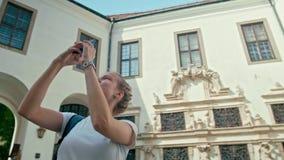 La muchacha turística en la camiseta blanca toma la foto panorámica por el teléfono en castillo almacen de video