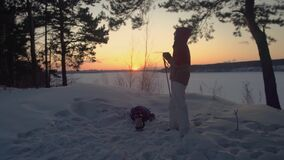 La muchacha turística está bebiendo té del termo en bosque nevoso del invierno adentro en la puesta del sol metrajes